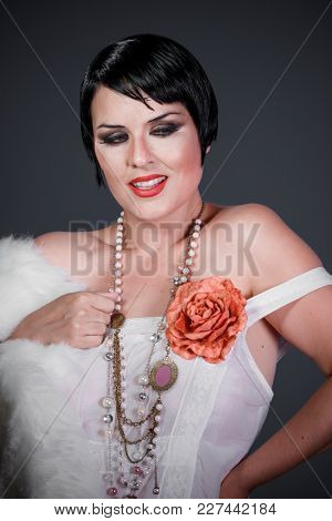 Fashion, Brunette girl with short hair, French mane in the style of the 20s. She wears white fur coat and jewelry