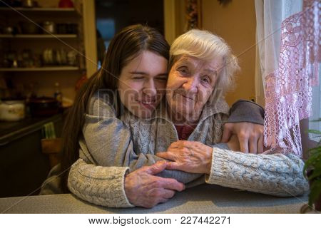 Portrait of an elderly woman with her adult granddaughter.