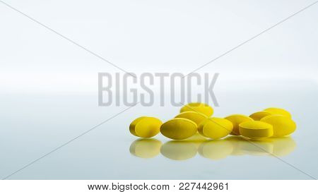 Pile Of Yellow Oval Tablet Pills On White Background With Copy Space For Text. Mild To Moderate Pain