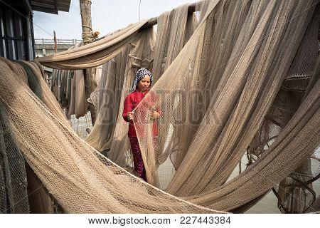 Ca Mau, Vietnam - Dec 6, 2016: Vietnamese Woman Mending Casting Net In Ngoc Hien, Ca Mau District, V
