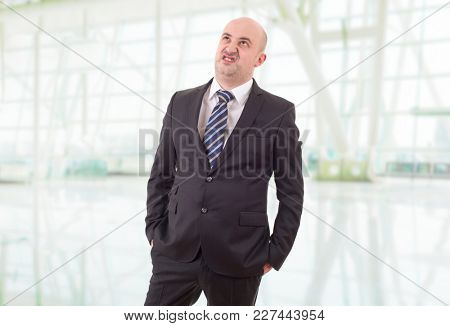 worried businessman in a suit looking up, at the office