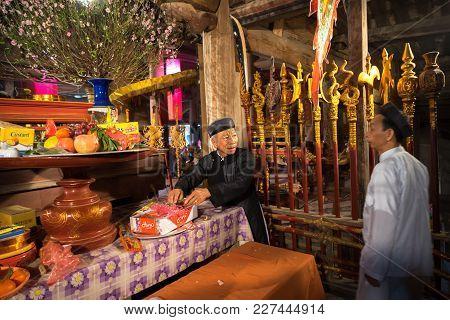 Hanoi, Vietnam - Jun 22, 2017: Old Man Preparing Worship Offerings On Altar On Holiday In Communal H