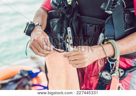 Diver Prepares His Equipment For Diving In The Sea
