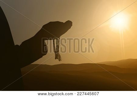Silhouettes Of Muslim People Praying To God With Sunset Background