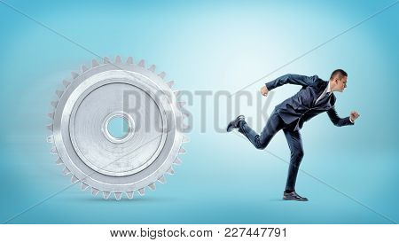 A Businessman Running Away From A Large Metal Spur Gear On A Blue Background. Industry And Commerce.