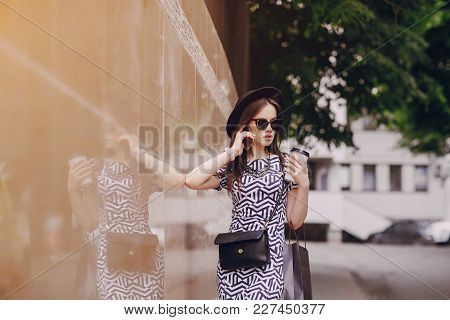 Young Model Holding A Coffee And Use The Phone