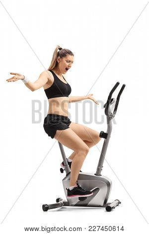 Full length profile shot of a displeased young woman exercising on a cross-trainer machine isolated on white background