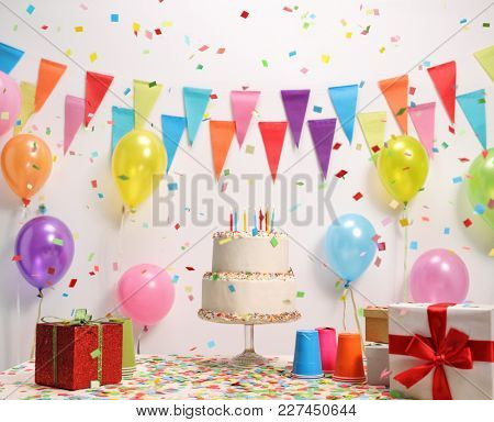 Birthday cake on a table against a wall with decoration flags and balloons