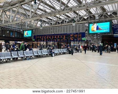 GLASGOW - FEBRUARY 19, 2018: People cross the main concourse inside Glasgow Central Train Station in Glasgow, Scotland, UK.