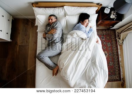 Interracial couple on the bed woman taking all the blanket