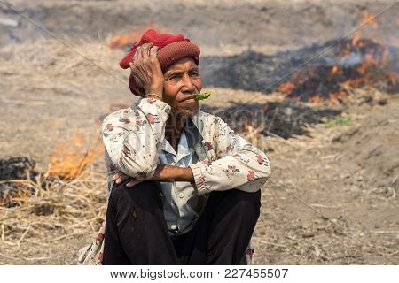 Gia Lai , Vietnam - March 12, 2017: Old Man Sit On Field With Fire Made With Dry Rice Straw In Gia L