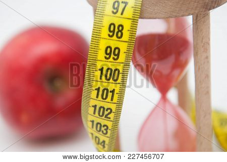 Lose Weight Concept. Red Apple And Tape Measure Close Up. Fat Burning And Weight Loss Process.