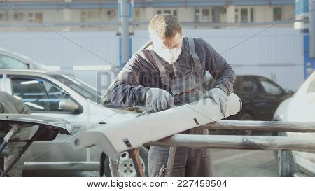 Man Worker In Automobile Service - Manual Labor - Polishes Car, Wide Angle