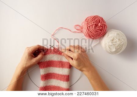 Female hands knitting with pink and white wool, top view. Knitting stripes with two colors of yarn.