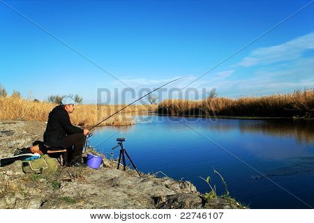 The Fisherman Is Fishing On The River