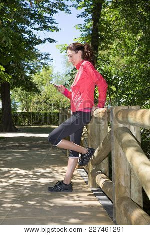Sporty Woman Using Smartphone In Wooden Footbridge