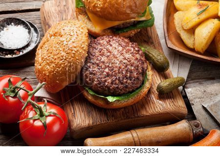 Tasty grilled home made burgers with beef, tomato, cheese, cucumber and lettuce