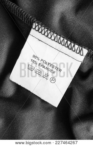 Content And Care Clothes Label On Black Textile Background Closeup