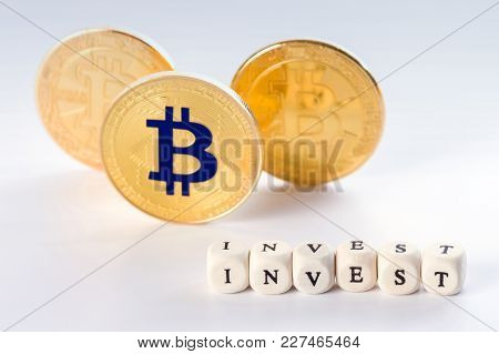 The Word Invest In Sharp Focus Made Of Wooden Blocks And Three Standing Bitcoin Coins Behind It. Inv
