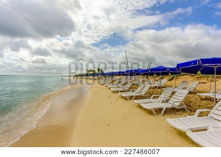 White Chaise Lounges And Blue Umbrellas Stand On A Beach In The Sand Near The Ocean With Green Waves