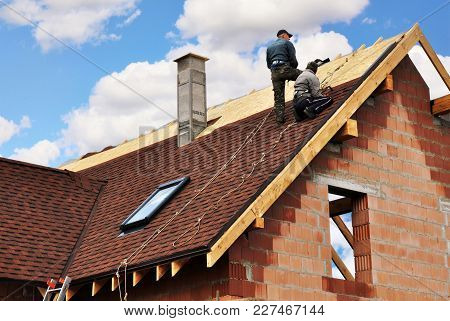 Kyiv, Ukraine - February, 20, 2018: Roofers Lay And Install Asphalt Shingles. Roof Repair With Two R