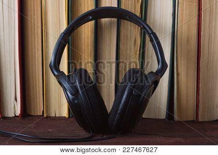Headphones Near The Folded Books On The Dark Wood Background