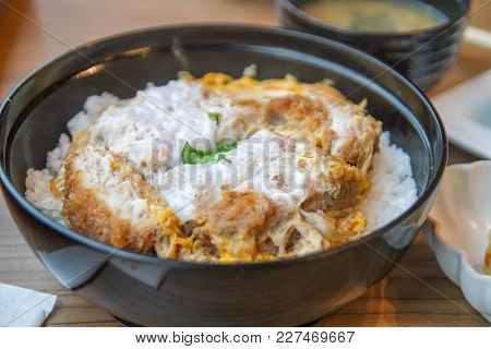 Katsudon Japanese Food, A Bowl Of Rice Topped With A Deep-fried Pork Cutlet, Egg, Vegetables, And Co