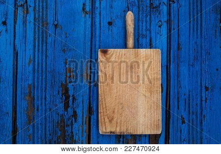 Old Chopping Cutting Board On Blue Wooden  Background. Empty Textured Kitchen Desk. Food Concept For