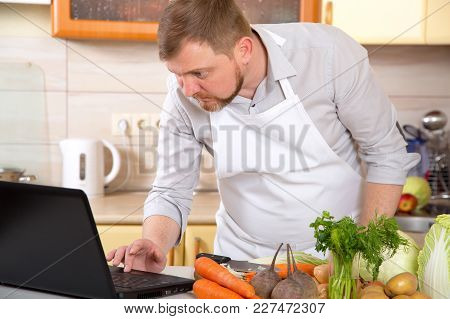 Adult Man Of 40 Years Old Prepares A Vegetable Dish In The Kitchen On A Prescription From The Intern
