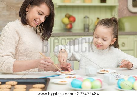 Mom And Her Daughter Baking Together And Decorating The Cookies.
