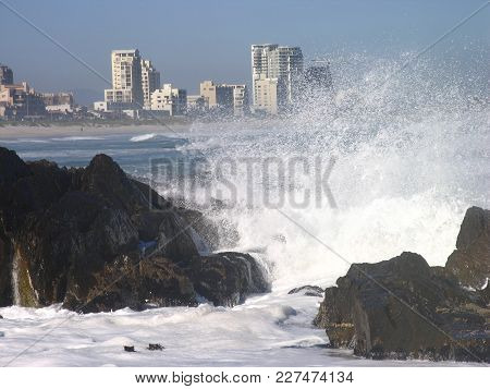 Winter Seascape, With Waves Crashing Over Some Rocks And Spraying Up  In To The Air In The Fore Grou