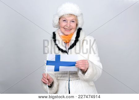 Senior Woman Holding A Flag Of Finland. Adult Woman Is 70 Years Of Age. Pensioner. Old Female Is Dre
