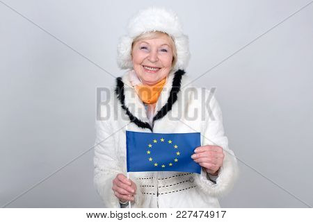 Senior Woman Holding A Flag Of European Union. Adult Woman Is 70 Years Of Age. Old Female Is Dressed