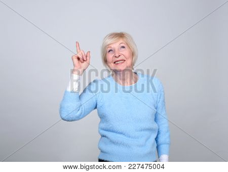 Senior Woman Is Pointing A Finger Up Above Her. Female 70 Years Of Age.