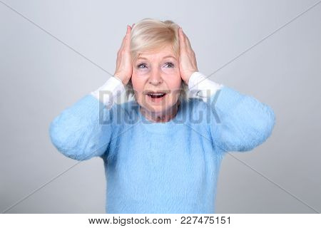Adult Woman Holds Her Hands To Her Head. Headache. Senior Woman 70 Years Of Age. She Is Not Listen,