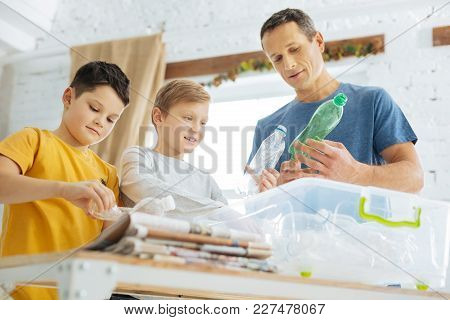 Caring About Nature. Charming Young Man And His Pre-teen Sons Preparing Plastic Bottles For Recyclin
