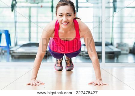 Frontal view of smiling young woman doing pushup in gym