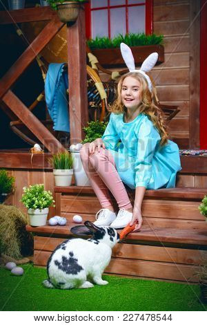 Easter holiday. Happy little girl is feeding a rabbit with a carrot on the porch near the wooden house. Rural style, easter decoration.