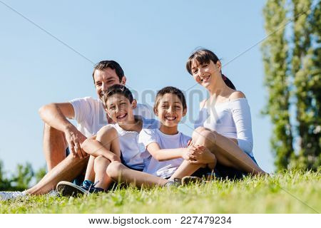 Happy family dressed in white in park in summer sitting in meadow