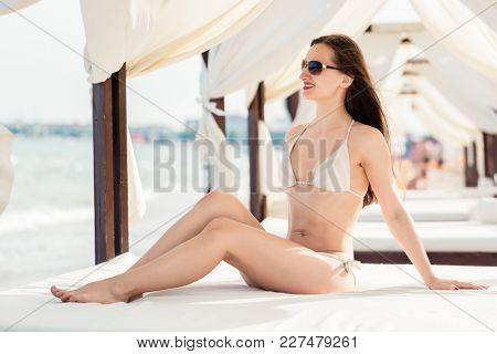 Woman in beach pavilion enjoying her summer vacation I the sun in swimwear