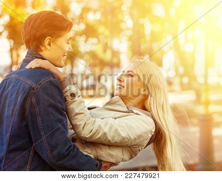 Spring couple walking park and kissing. Summer friends walk outdoor. First date and kiss of two young people in good weather day. Sunlight in sunset or sunrise. Beginning of first love.