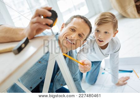 Eager To Help. Excited Pre-teen Boy Checking The Length Of A Table Leg By Looking At The Tape Measur