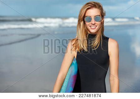 Beautiful Happy Female Wears Black Bikini And Sunglasses, Poses For Women`s Magazine On Coastline, C