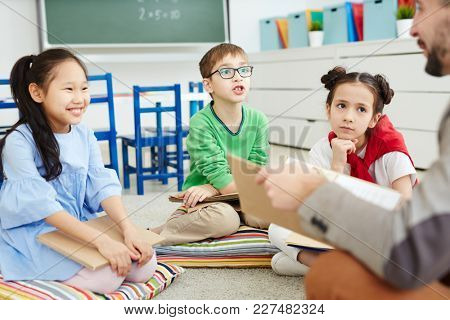 Group of schoolchildren discussing book with their teacher at lesson of literature