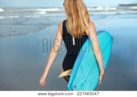 Back View Of Slim Blonde Woman Wears Swimsuit, Keeps Surf Board Under Arm, Walks On Bay With Surfboa
