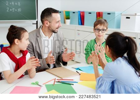 Group of cute schoolkids and their teacher discussing size of something at lesson
