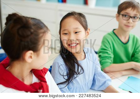 Cute intercultural schoolgirls having talk at lesson with their classmate on background