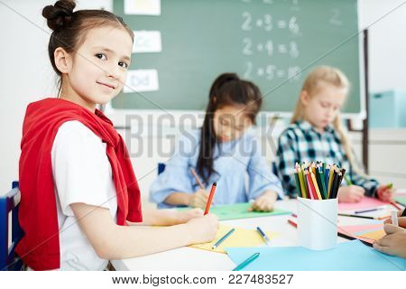 Diligent schoolgirl looking at camera while drawing with crayons and highlighters