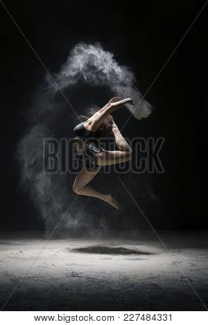 Woman In Black Shorts And Top Jumping Gracefully In A White Dust Cloud Profile Shot In Dark Room
