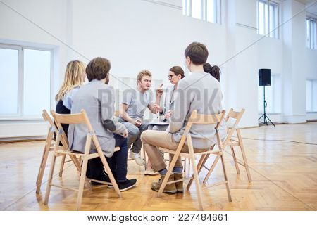 Irritated young man trying to explain his problems to psychologist among groupmates during session